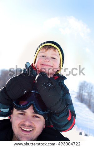 Winter outdoor portrait of a happy father and son on ski slopes