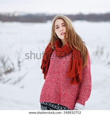 winter outdoor portrait of cute young pretty blond girl with red sweater and scarf looking to camera on natural field background. Cloudy weather. Lifestyle - stock photo