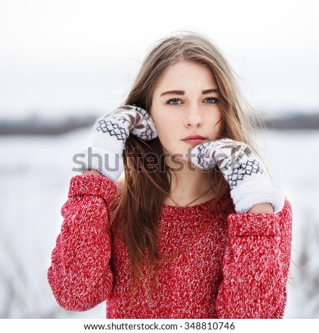 winter outdoor portrait of cute young pretty serious thoughtful blond girl with red sweater and white mittens looking to camera and fixing hair on natural field background. Cloudy weather - stock photo