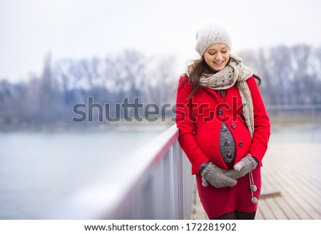 Winter outdoor portrait of pregnant woman in fashionable clothes standing by the river - stock photo