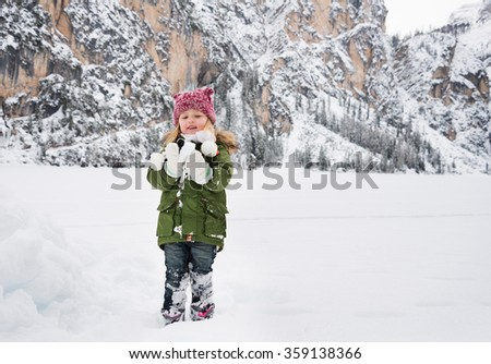 Winter outdoors can be fairytale-maker for children or even adults. Happy child in green coat playing with snow. Mountains in the background
