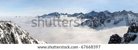 Winter panorama of mountains above the clouds. View of the High Tatras from Zadni Granat. - stock photo