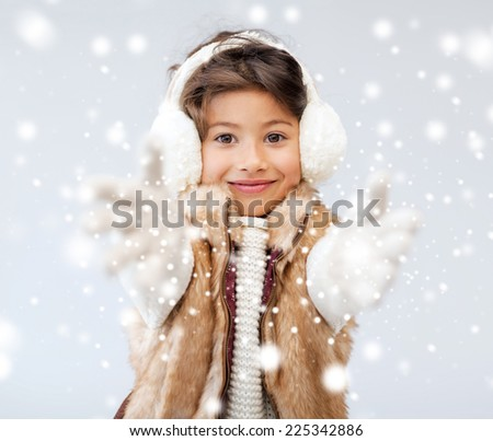 winter, people, childhood and happiness concept - happy little girl in winter clothes - stock photo