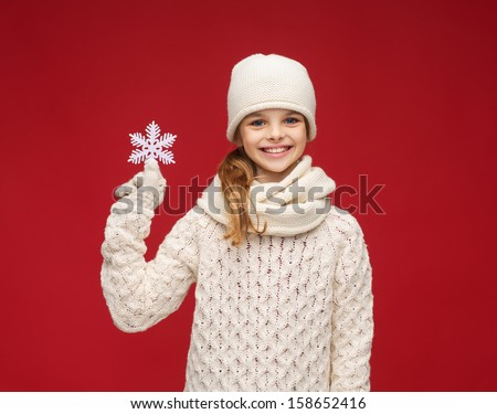 winter, people, happiness concept - girl in hat, muffler and gloves with big snowflake - stock photo