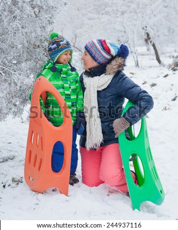 Winter, play, fun - Mother and her cute little son having fun with sled in winter park