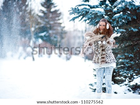 winter portrait of a beautiful girl in snowy forest - stock photo