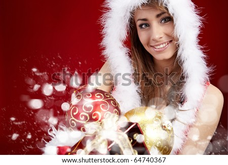 winter portrait of a beautiful young smiling woman with a gift in her hands - stock photo