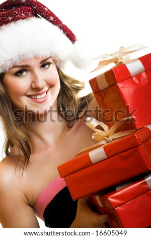 winter portrait of a beautiful young smiling woman with some christmas gifts - stock photo