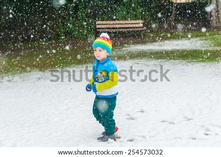 Winter portrait of a cute little boy under the snowfall, wearing christmas pullover and colorful hat  - stock photo