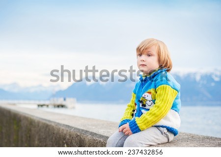 Winter portrait of a cute little boy, wearing funny warm knitted jacket with snowman, sitting by the lake against mountains - stock photo