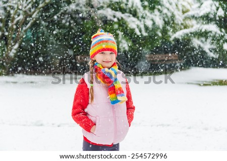 Winter portrait of a cute little girl under the snowfall, wearing red pullover, colorful hat and scarf - stock photo