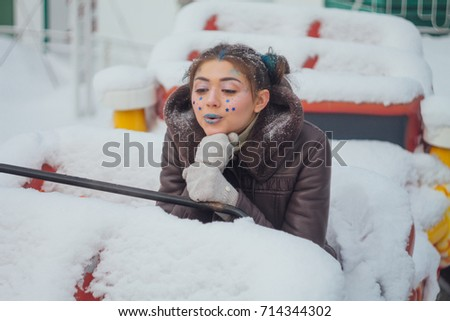 Winter portrait of a girl with bright make up and blue stars on face with barberry