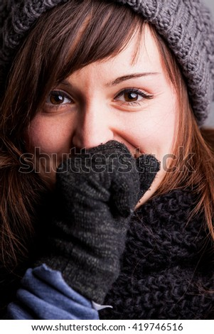 winter portrait of a happy woman with wool hat scarf and gloves