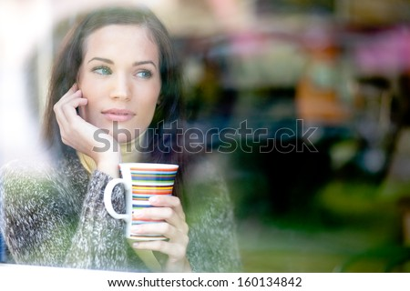 Winter portrait of a young woman looking out the window enjoying a hot cup of tea / coffee  - stock photo