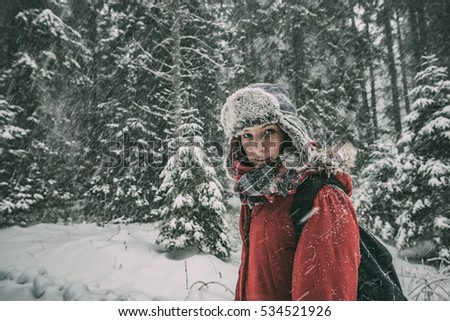 Winter portrait of beautiful young traveler in snowy forest