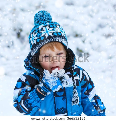 Winter portrait of cute kid boy in colorful clothes, outdoors during snowfall. Active outoors leisure with children in winter on cold snowy days. Happy toddler child having fun with snow in forest - stock photo
