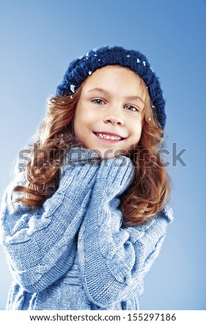 Winter portrait of cute little girl wearing warm cosy clothes studio shot with snow