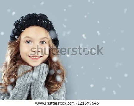 Winter portrait of cute little girl wearing warm cozy clothes studio shot with snow
