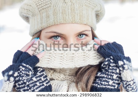 Winter Portrait of Female with Beautiful Blue Eyes outdoor. Closeup of Young woman wearing clothing for cold weather a scarf hat and gloves. - stock photo