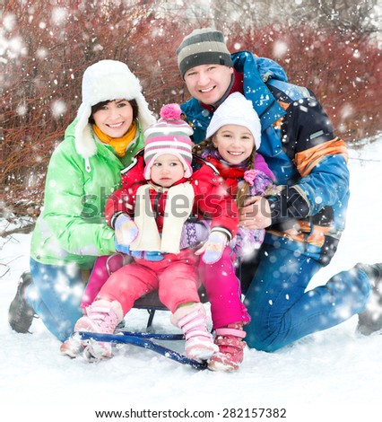Winter portrait of happy young family of 4 people - stock photo