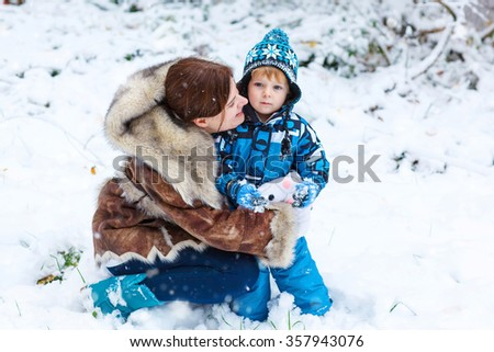 Winter portrait of kid boy and mother in colorful clothes, outdoors during snowfall. Active outoors leisure with children in winter on cold snowy days. Happy woman and son having fun with snow - stock photo