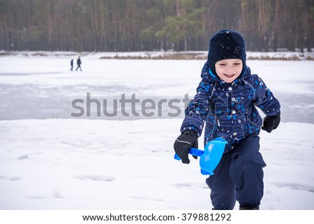 Winter portrait of kid boy in colorful clothes, outdoors during snowfall. Active outoors leisure with children in winter on cold snowy days. Happy toddler child having fun with snow in forest - stock photo