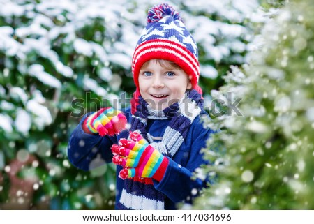 Winter portrait of little kid boy in colorful clothes, outdoors during snowfall. Active outdoors leisure with children in winter on cold snowy days. Happy child having fun with snow - stock photo