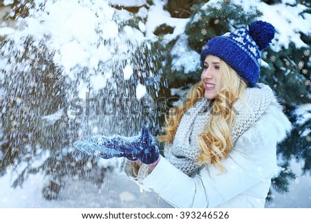 Winter portrait of young beautiful blond woman in her warm clothing in the forest. Snowy effect - stock photo