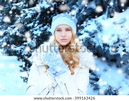 Winter portrait of young beautiful blond woman in her warm clothing in the forest. Snowy effect