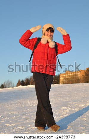 Winter portrait of young woman posing on hill and gesturing - stock photo