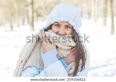 Winter Portrait of Young Woman wearing clothing for cold weather at snow day. Happy Caucasian female wintertime season outdoor. - stock photo