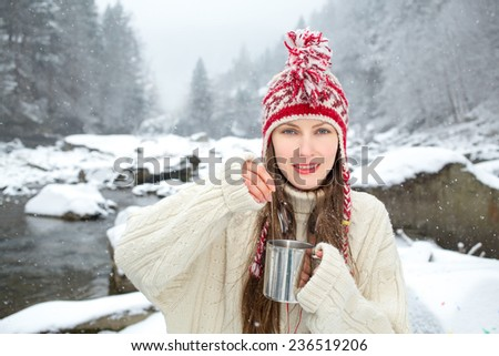 winter portrait woman drinking hot tea over amazing snowy landscape