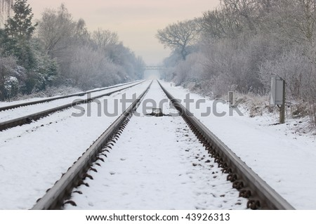 winter railroad track diminishing into a distant hazy sunset (portrait crop also available) - stock photo