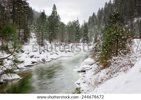 winter river with snow falling and slow shutter speed off mountainous highway - stock photo