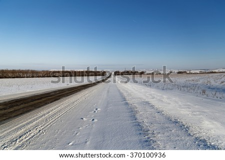 Winter road among snowy fields. Field and trees in the distance far away.