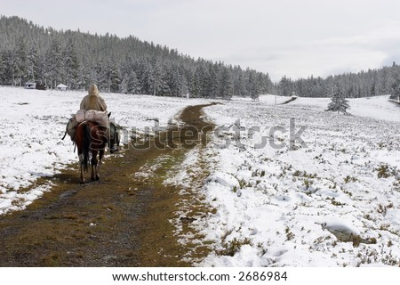 Winter road and horseman. Altay. Russia. - stock photo