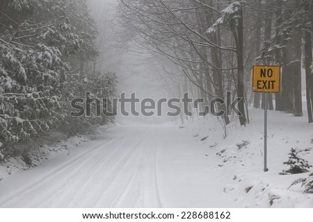 Winter road and trees covered in snow with Yellow No Exit sign - stock photo