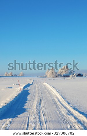 Winter road in snowy countryside landscape - stock photo