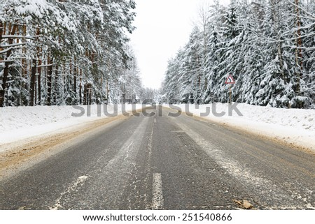 Winter road in snowy frosty forest landscape - stock photo