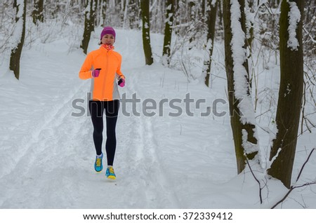 Winter running in forest: happy woman runner jogging in snow, outdoor sport and fitness concept  - stock photo