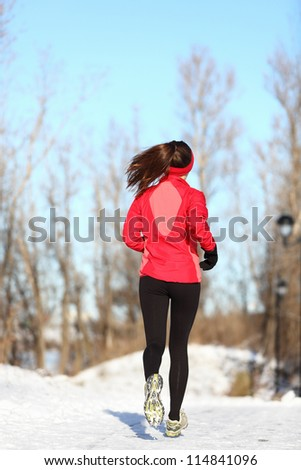 Winter running woman jogging in snow. Female runner in full body. Active lifestyle and wellness concept with young woman fitness model. - stock photo