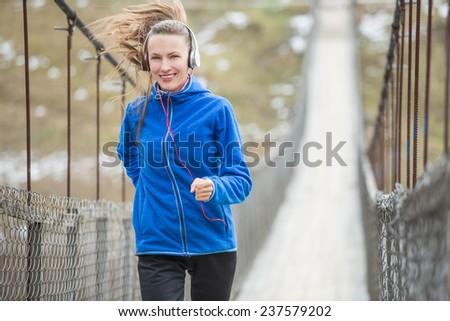 Winter running woman running on old rural bridge. motion, daylight - stock photo