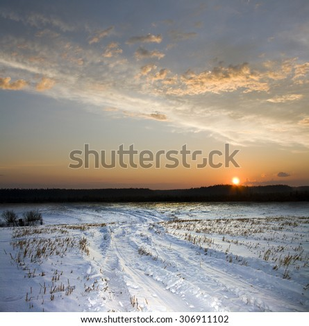 Winter rural road to sunset. Freeze field - stock photo
