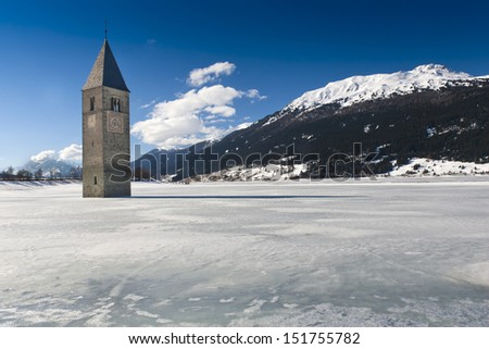 Winter scene at Lake Reschen with sunken gray steeple. Lake Reschen is an artificial lake located in the western portion of South Tyrol, Italy, near the Reschen Pass. - stock photo