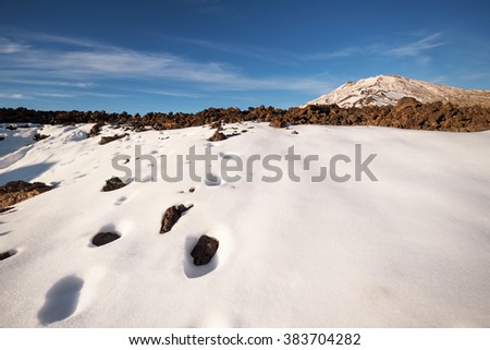 Winter scene of Teide national park at sunset with volcanic rocks and snow, in Tenerife, Canary islands, Spain. - stock photo