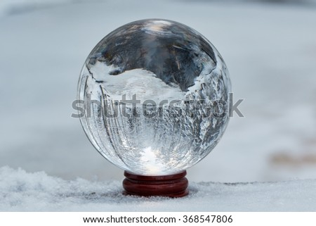 Winter scene with a transparent crystal ball reflecting the snowy landscape. Icy river appearing upside down on the ball. - stock photo