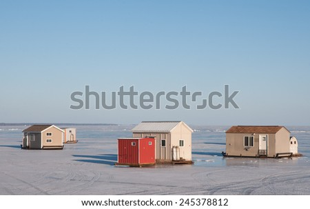 Winter scenery: Ice fishing houses on frozen lake