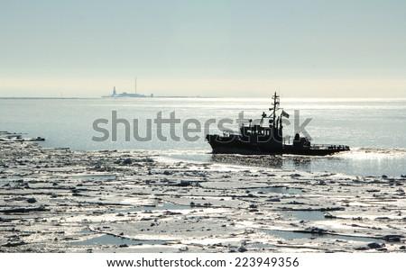 Winter sea scene: ship going through ice cover near  Suomenlinna island in Finish bay of Baltic sea near Helsinki, Finland - stock photo