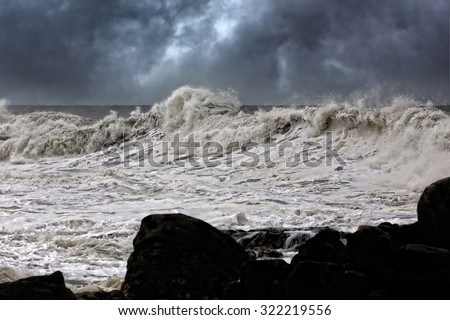 Winter seascape with big waves and dark dramatic sky. Enhanced sky. Northern portuguese coast. - stock photo