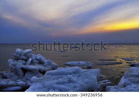 Winter seascape with ice floes been washed ashore - stock photo